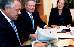 Joe Hockey, Mathias Cormann and Kelly O'Dwyer gather around the Intergenerational Report in March. © Mick Tsikas / AAP