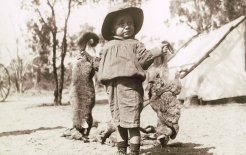 A young boy holding two dead possums at a trappers camp in the Blackall district, Queensland, 1908