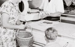 Mrs Austin and son visit the butcher in 1951. Courtesy of the National Archives of Australia