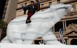Aided by Purves Environmental Fund, sculptor Mark Coreth rides his life-sized ice polar bear in Sydney, 3 June 2011. © Reuters/Daniel Munoz